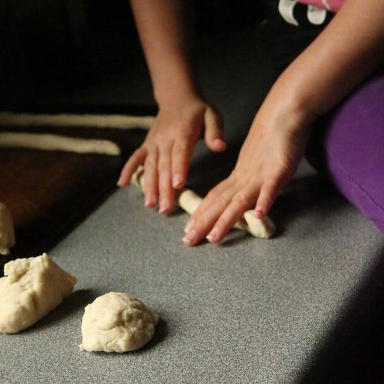 Rolling dough into pretzels
