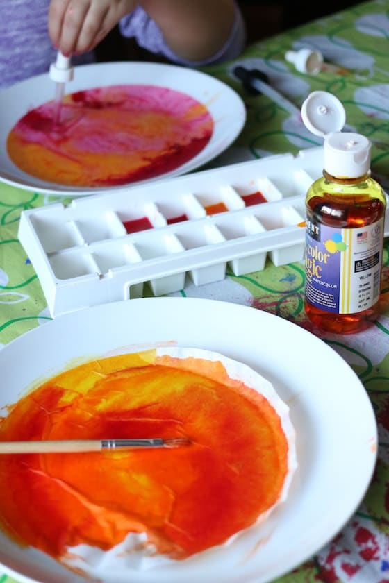 painted orange coffee filter beside ice cube tray filled with yellow red and orange liquid watercolours
