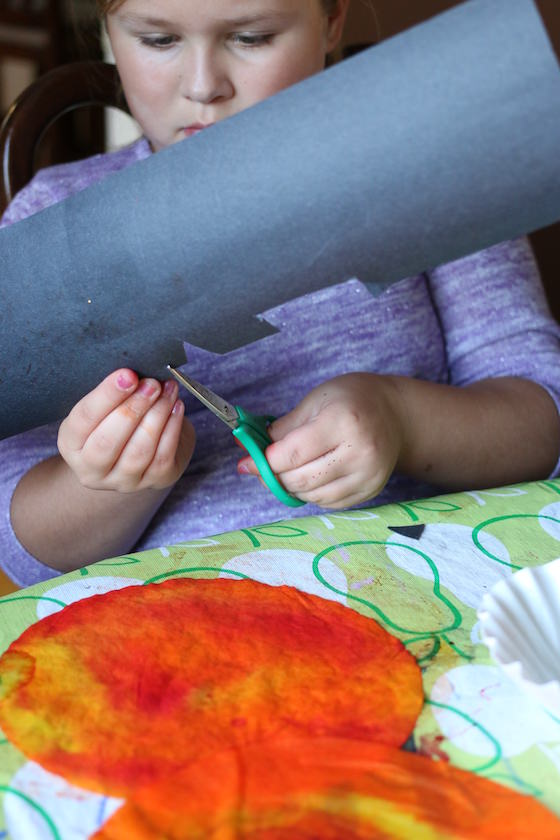 child cutting pumpkin eyes and mouth out of black construction paper