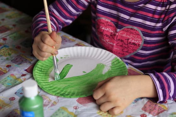 Child painting paper plate green