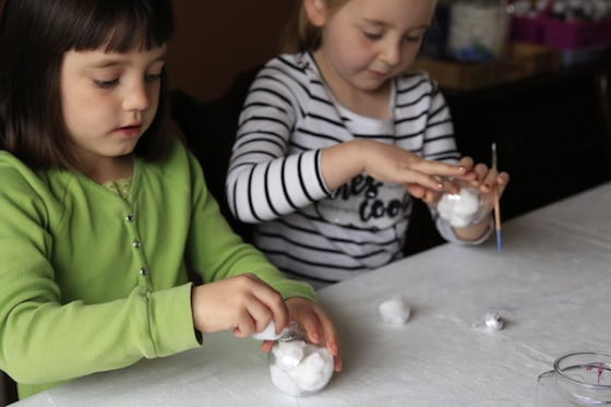 2 girls stuffing ornaments with cotton balls