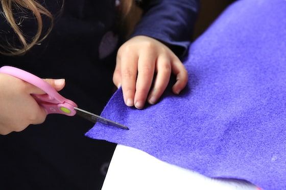 Child cutting purple felt