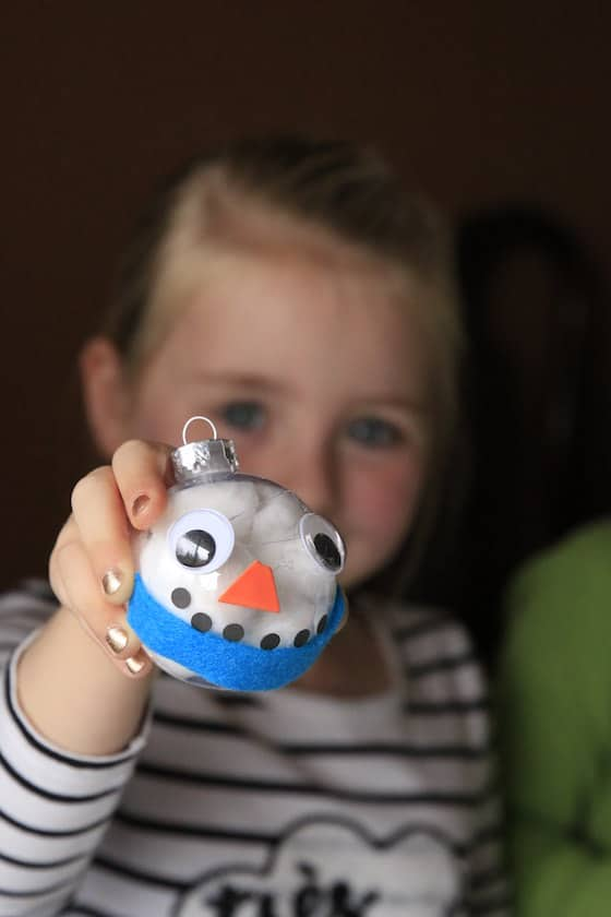 Girl holding out finished snowman ornament with blue scarf