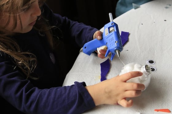Child gluing purple scarf to snowman