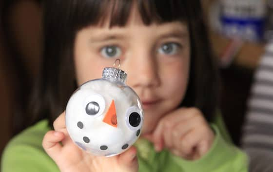Child holding finished snowman ornament