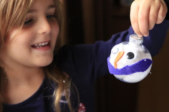 Child holding up finished snowman ornament with purple scarf