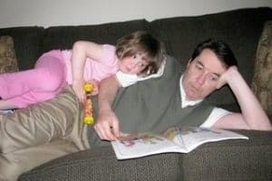 girl and dad reading together