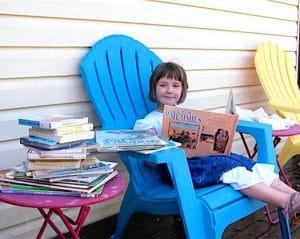 young girl reading and surrounded by books
