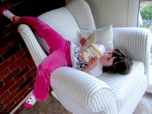 girl sprawled upside down in a chair reading BFG