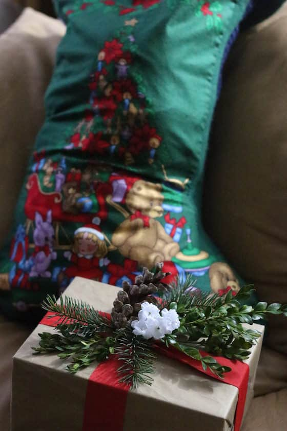 Inexpensive brown paper-wrapped gift in front of stocking