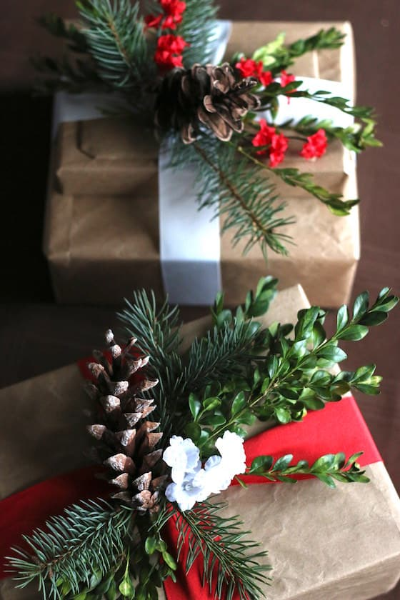 Beautiful gifts wrapped with paper bags, ribbon, pinecones and greenery.