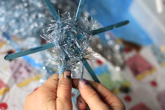making snowflake ornament by weaving fuzzy yarn around craft sticks