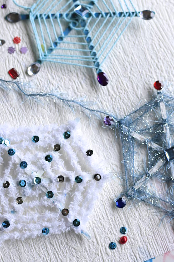3 snowflake ornaments with yarn and craftsticks