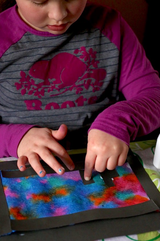 9 year old making gluing black paper to coloured paper towels