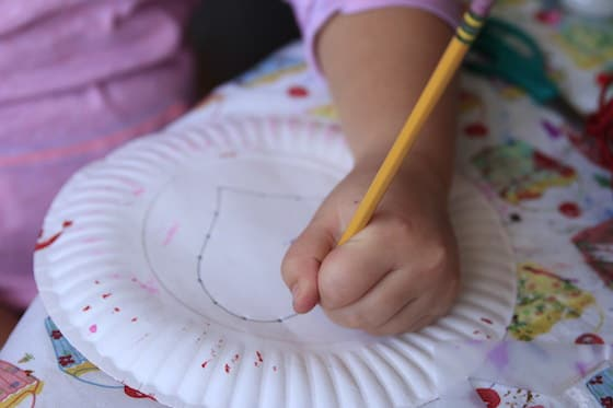 Kid poking holes in a paper plate
