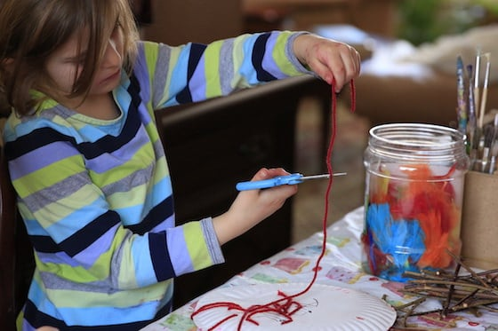 5 year old cutting red yarn with scissors