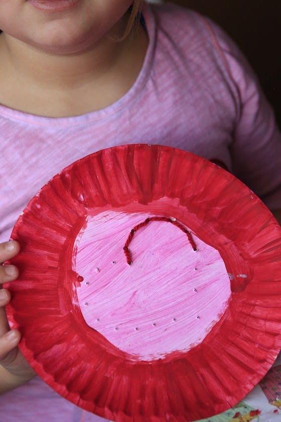 Child backstitching a heart onto a paper plate