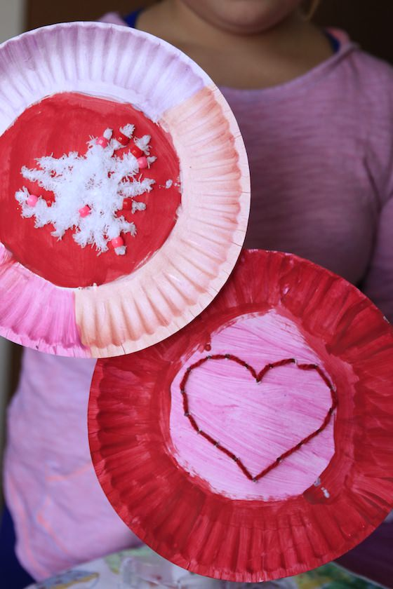10 year old holding up 2 paper plates decorated for Valentines day