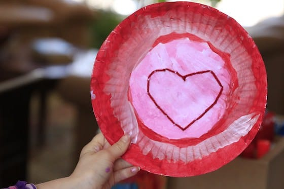 Child holding up red and pink paper plate