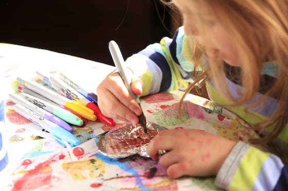 Child colouring on tinfoil with a Sharpie marker