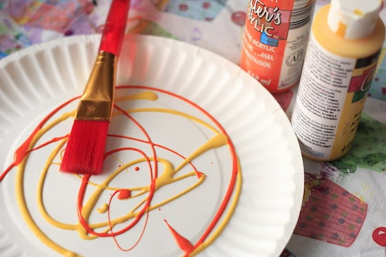 yellow and orange paint on paper plate