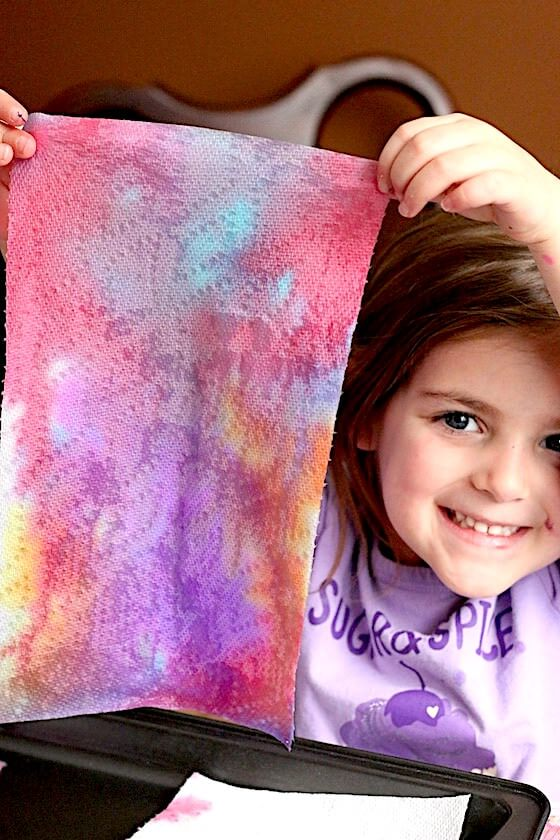 Preschooler holding up art project