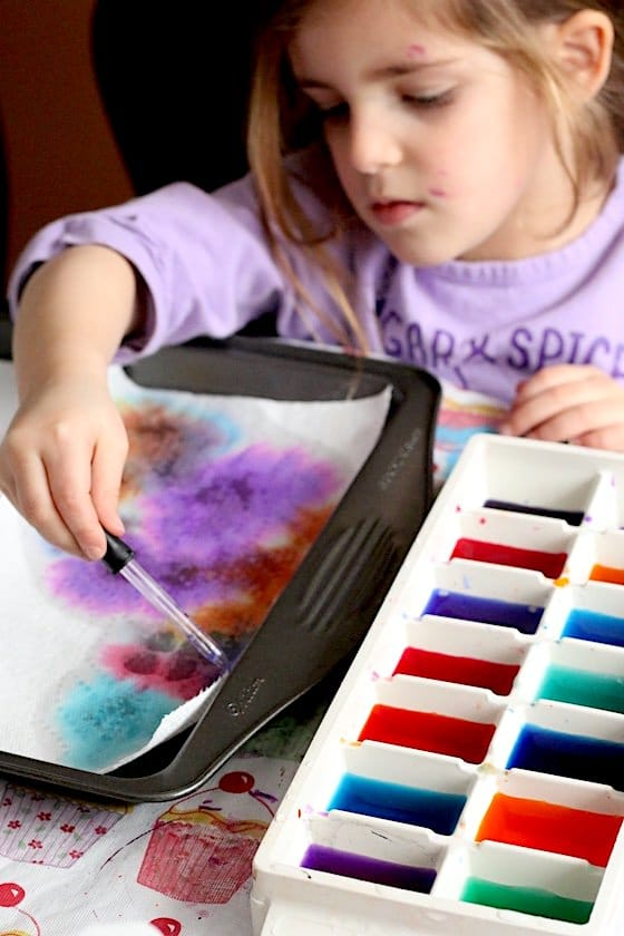 Preschooler making drip art with liquid watercolours
