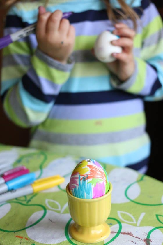 Child colouring egg with sharpies