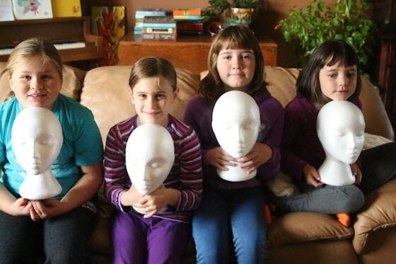 4 kids holding white styrofoam mannequin heads
