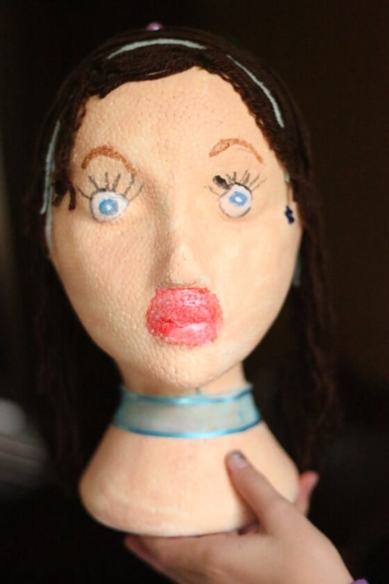 Styrofoam mannequin head decorated by child