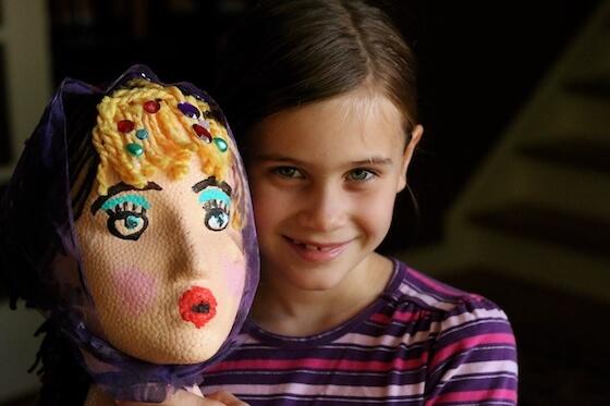 Girl holding decorated styrofoam head