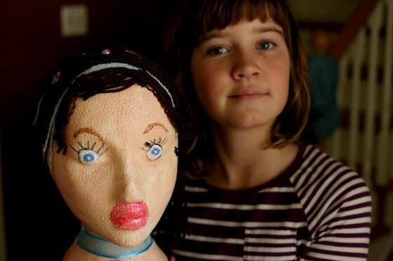 girl holding styrofoam head painted to look like herself