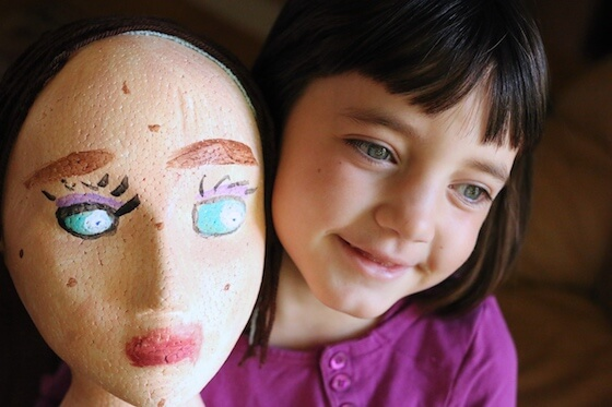 Girl holding styrofoam mannequin head painted as self-portrait