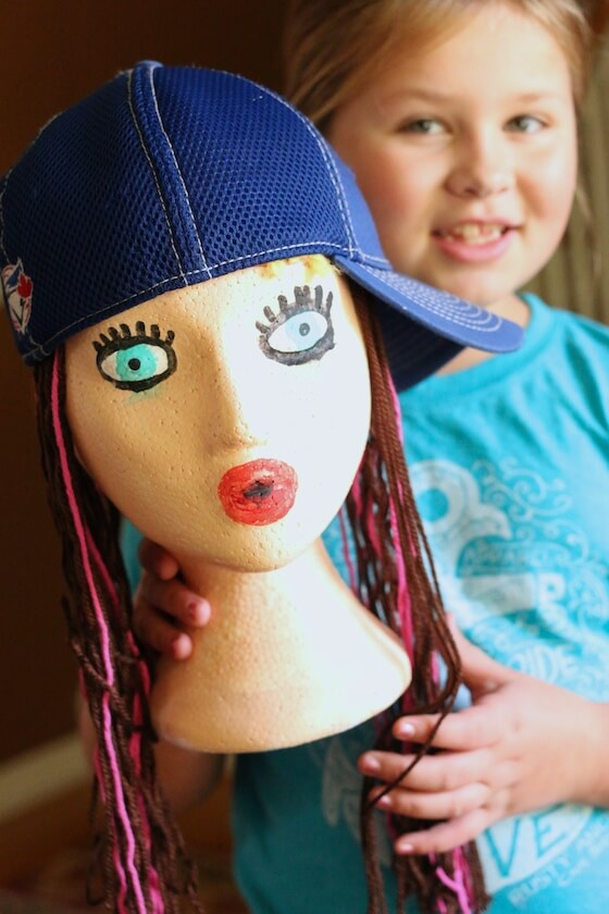 girl holding styrofoam head decorated and wearing ball cap