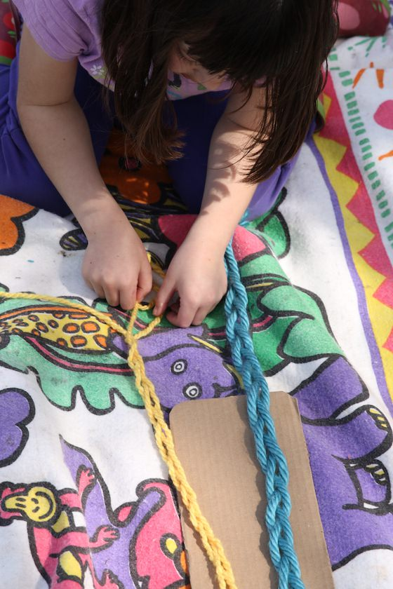 7 year old braiding yarn on a blanket in the backyard