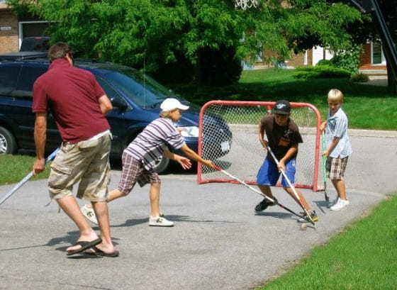 dad and kids playing road hockey
