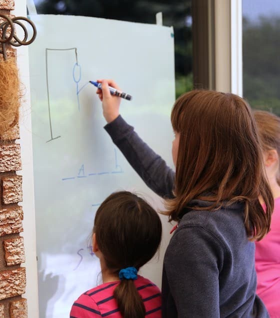 Kids playing hangman on sliding glass door