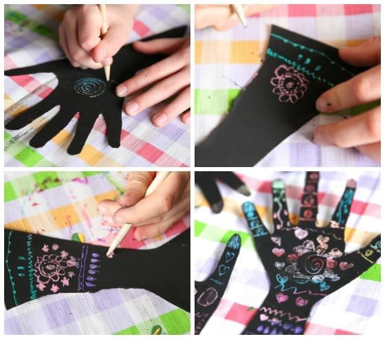 Kids making henna hand art with scratch art technique