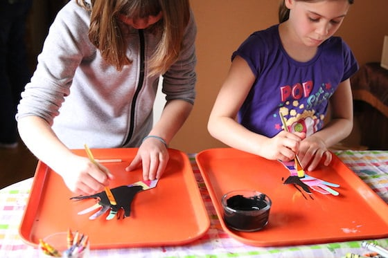 kids painting over coloured hands with black paint