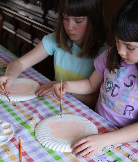 kids painting paper plates with skin-toned paint