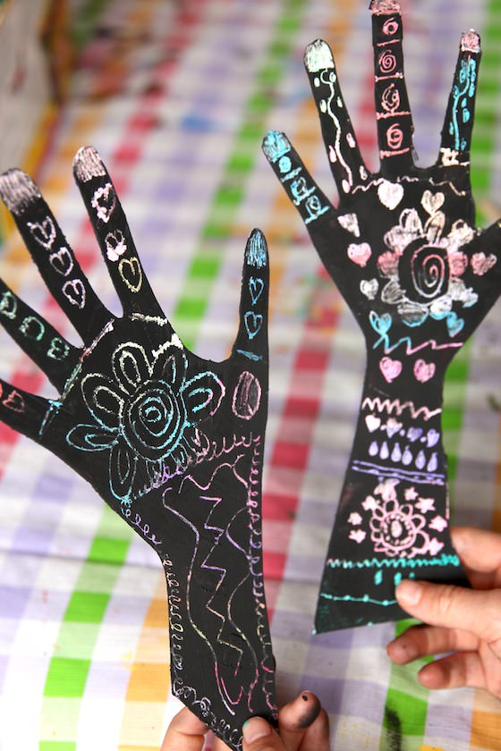two kids' hands decorated with henna scratch art