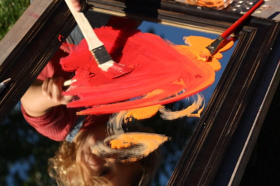 paintbrush and red and orange paint on mirror