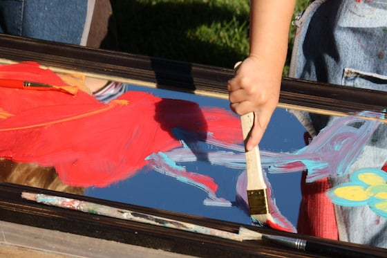 preschooler painting on a mirror with a brush