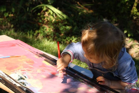 2 year old painting on mirror under tree
