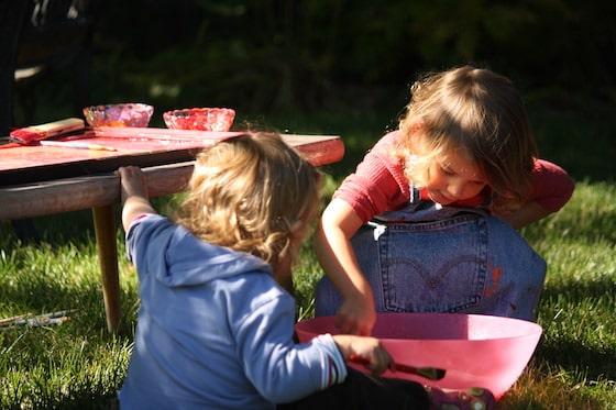 kids washing paintbrushes in bowl of water