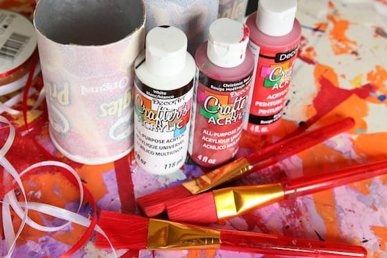 Pringles cans, red and white paint, ribbon, paintbrushes