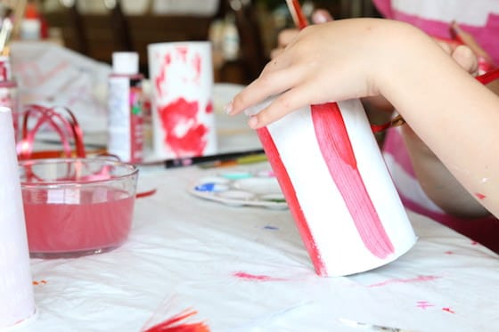 Kids painting pringles cans red and white
