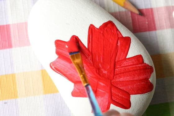 Painting a maple leaf on a beach rock