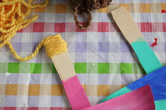 gluing yarn to paint stick