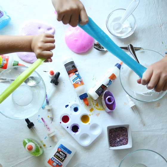 kids stretching Elmer's glue slime over table of slime ingredients